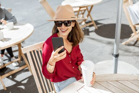 Portrait of a stylish woman sitting with phone and coffee cup at the cafe terrace during a sunny day Foto de archivo