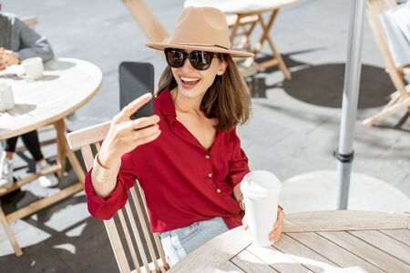 Portrait of a stylish woman sitting with phone and coffee cup at the cafe terrace during a sunny day