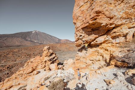 Beautiful rocky landscape on the volcanic valley with unrecognisable climbers and Teide volcano on the background during a sunny day