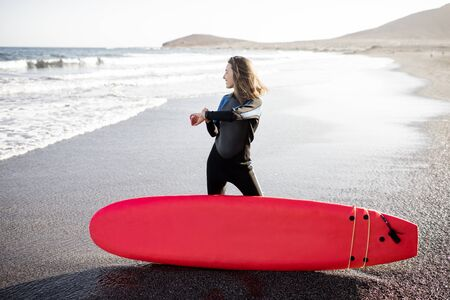 Young surfer in wetsuit standing with surf board on the wild beach on a sunset, looking on smart watch. Concept of using smart gadgets in sport