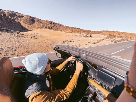Man driving convertible car while travel on the desert road. Image made on mobile phone