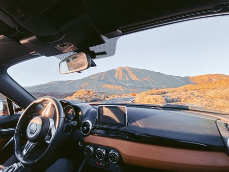 Car on the desert road, view from the car interior. Image made on mobile phone focused on the beautiful road and volcano on the background