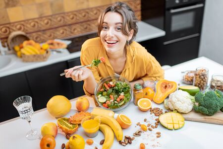 Portrait of a young cheerful woman eating salad at the table full of healthy raw vegetables and fruits on the kitchen at home. Concept of vegetarianism, healthy eating and wellness