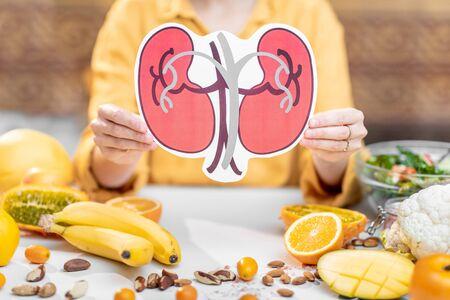 Menselijk niermodel met een verscheidenheid aan gezond vers voedsel op tafel houden. Concept van uitgebalanceerde voeding voor de gezondheid van de nieren