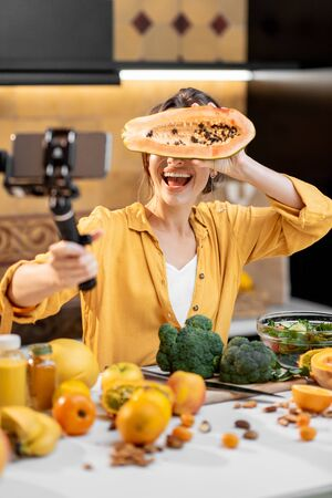 Young and cheerful woman vlogging on mobile phone about healthy food and cooking. Concept of healthy eating and social media influencing