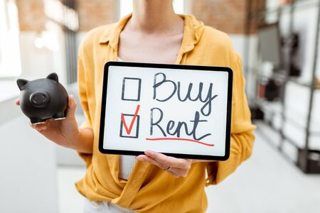 Woman decides between buying or renting real estate, holding saving pig and digital tablet indoors. Concept of choosing the right housing solution Stockfoto