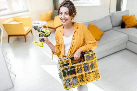 Portrait of a young and beautiful handy woman standing with a screwdriver and instrument box at the living room of apartment. Woman ready for the house repairment or improvement