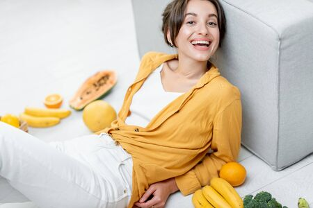 Portrait of a young and cheerful woman sitting with lots of fresh fruits and vegetables on the floor at home. Photo carried in yellow color. Concept of wellbeing, healthy food and homeliness