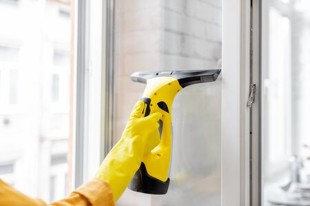 Woman washing windows with a special cleansing device at home, close-up on eqipment. Concept of a professional housekeeping