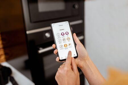 Controlling smart kitchen appliance using mobile phone at home, close-up on mobile screen. Concept of a smart home and managing home with mobile devices Stock Photo