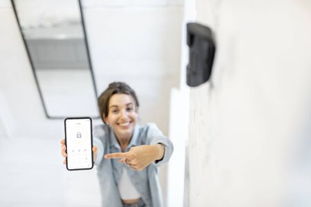 Woman controlling alarm system with a smart phone, showing phone with launched mobile application. View from above with motion sensor on the foreground