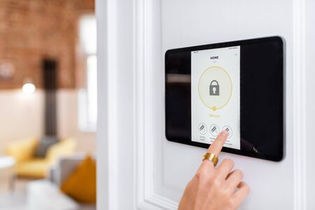Controlling home alarm system with a digital touch screen panel installed on the wall. Concept of wireless secure control and smart home