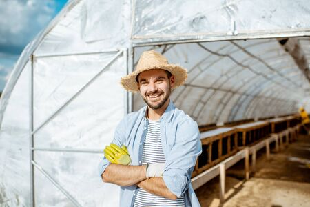 Portrait of a handsome farmer standing in front of the hothouse on a farm with snail breeding outdoors