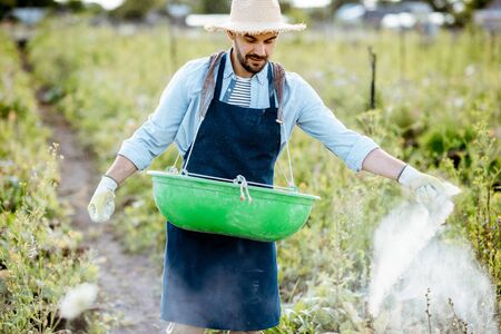 Handsome farmer feeding snails, walking on the field with green buskets and powdering feed. Concept of farming snails for eating