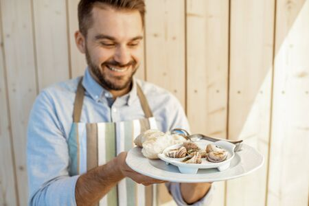 Portrait of a handsome waiter with delicious dish, holding a plate with stuffed snails and bread on the wooden background Stockfoto