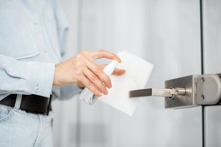 Woman in protective gloves disinfecting door handle while cleaning at home, close-up view on hands. Concept of prevention of virus spread during an epidemic