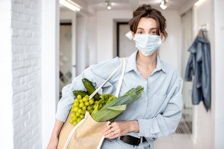 Young woman in medical mask coming home with shopping bag full of fresh food. Concept of lifestyle during an epidemic or bad air pollution