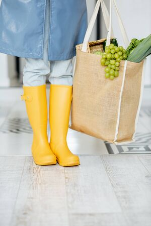 Woman in yellow rubber boots and raincoat standing with shopping bag full of fresh food in the corridor. Woman coming home in rainy weather