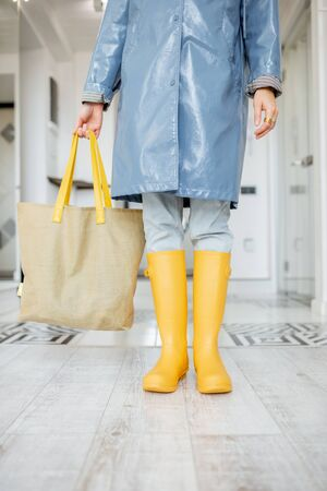 Woman in yellow rubber boots and raincoat standing with shopping bag in the corridor at home, ready to walk outside in rainy weather Stock Photo