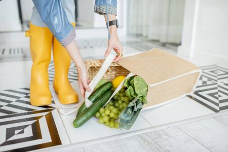 Shopping bag full of fresh vegetables and greens which fell on the floor in the corridor at home, woman in yellow rubber boots