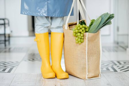 Woman in yellow rubber boots and raincoat standing with shopping bag full of fresh food in the corridor. Woman coming home in rainy weather Stock Photo - 143137796
