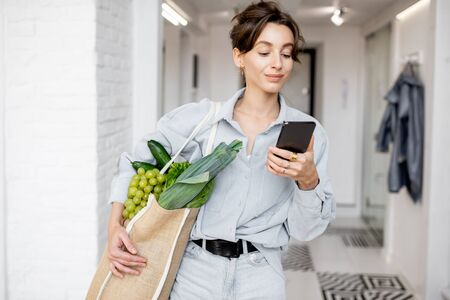 Portrait of a young and cheerful woman standing with mobile phone and shopping bag full of fresh food at home. Concept of buying products online