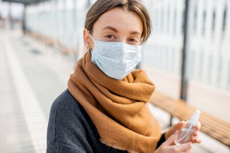 Portrait of a young depressed woman in face mask during an epidemic outdoors. Concept of social isolation during Coronavirus epidemic