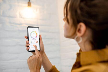 Contrôler la température et l'intensité de l'ampoule avec une application pour smartphone. Concept d'une maison intelligente et gestion de la lumière avec des appareils mobiles Banque d'images