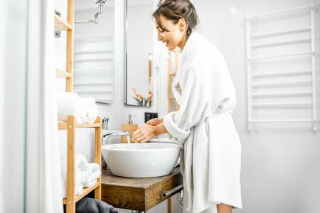 Young and cheerful woman dressed in white bathrobe having some hygienic procedures, washing hands in the bathroom at home 写真素材