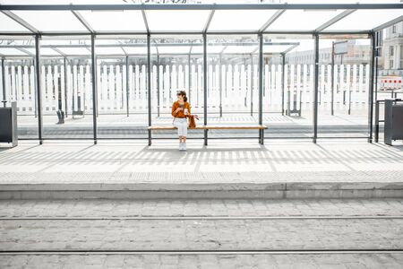 Woman sitting alone at the public transport stop on a sunny day outdoors, general plan on a modern stop. Concept of a transportation and urban life Banque d'images