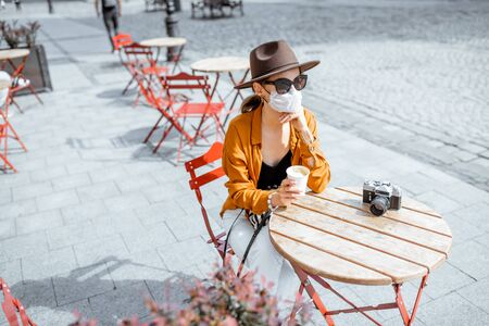 Young woman in facial mask sitting on the cafe terrace alone. Concept of social distancing and new social rules after coronavirus pandemic. 免版税图像