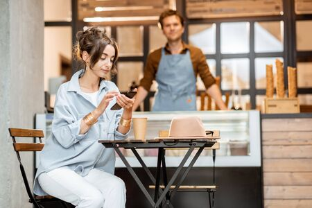 Young female customer sitting with phone at the cafe or pastry shop with a seller on the background Stock Photo