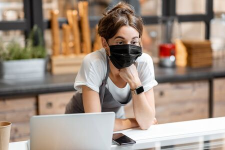 Portrait of a saleswoman or small business owner wearing medical mask at the counter in cafe or small shop. Concept of a retail business during a pandemic Archivio Fotografico