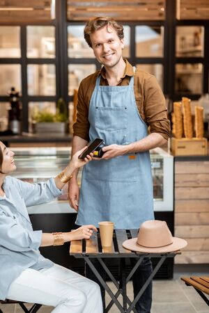 Happy waiter with a client at the cafe or ice-cream shop, making contactless payment with a smartphone Stock Photo