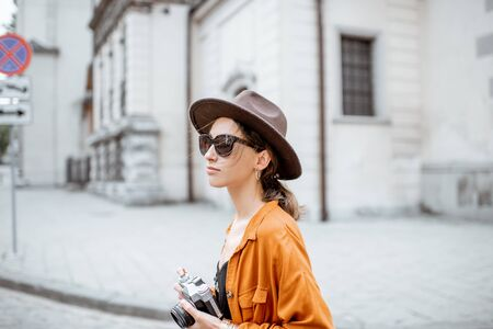 Portrait of a young stylish woman with photo camera traveling old city street. Concept of happy traveling and summer vacations in the european town