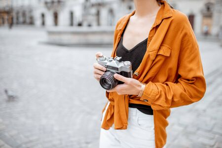 Woman holding vintage camera while traveling in the city, close-up view focused on camera