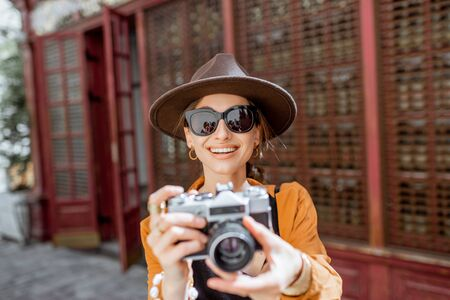 Portrait of a young stylish woman with vintage photo camera, traveling in the old city street with beautiful old cafe facade on the background