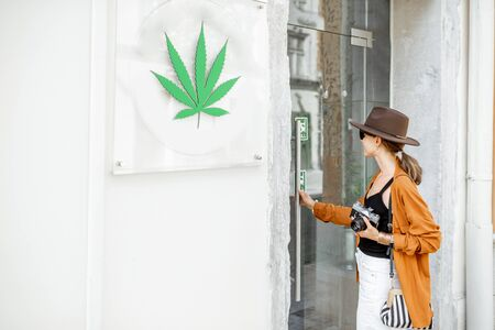 Woman visiting coffee shop or store with cannabis, while traveling. Concept of legalization of marijuana for tourism