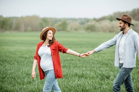 Pregnant woman with her man having fun together, walking on the greenfield. Happy couple expecting a baby, young family concept