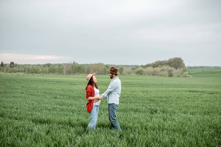 Portrait of a pregnant woman with her boyfriend dressed casually with hats standing together on the greenfield. Happy couple expecting a baby, young family concept Фото со стока