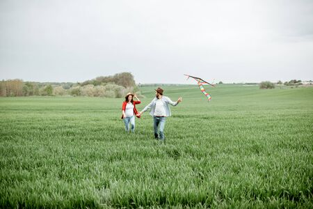 Happy couple having fun together, playing with kite on the greenfield. Happy couple expecting a baby and young family concept