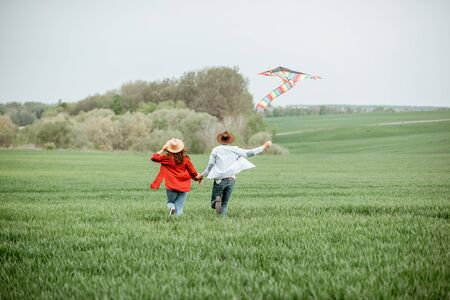 Happy couple having fun together, playing with kite on the greenfield. Happy couple expecting a baby and young family concept Фото со стока - 150295930