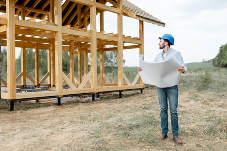 Architect or builder with blueprints on the construction site outdoors. The concept of building and designing a wooden frame house