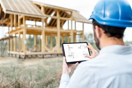 Architect or builder using digital touchpad on the construction site outdoors. Close-up on screen with copy space