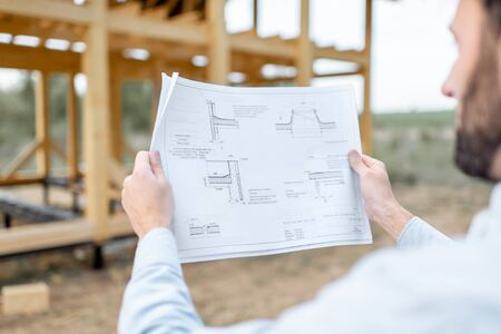 Builder looking on teh drawings of wooden house structures on the construction site. Concept of building and designing wooden frame house