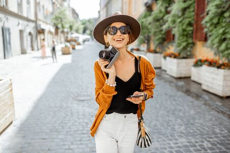 Portrait of a young stylish woman with photo camera and phone traveling old city street. Concept of happy traveling and communication