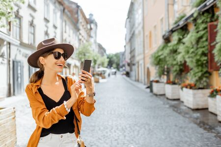 Young stylish woman with a smart phone on the old city street. Concept of happy traveling and summer vacations in the european town