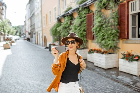 Young stylish woman making selfie with a smart phone on the old city street. Concept of happy traveling and summer vacations in the european town