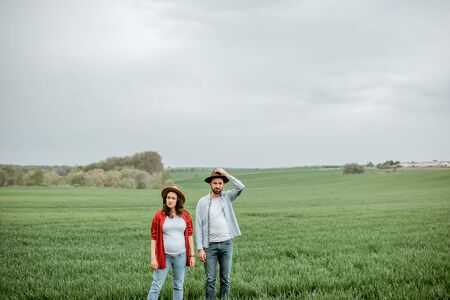 Portrait of a lovely couple standing together on the greenfield. Happy couple expecting a baby, young family concept