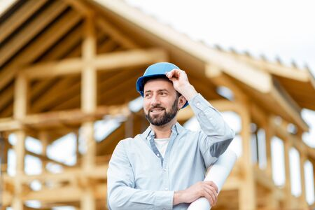 Portrait of an architect or builder in hard hat standing in front of the wooden house structure. Building and designing wooden frame house concept 免版税图像